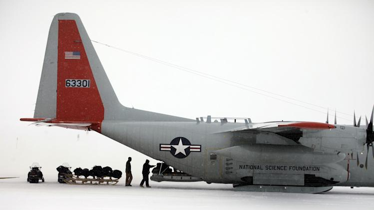 In this July 15, 2011 photo, on the world's longest ice runway, 16,800 feet long, logistics workers offload cargo from a New York Air National Guard LC-130 transport plane mounted with landing skis, at Summit Station, a remote research site operated by the U.S. National Science Foundation (NSF), situated 10,500 feet above sea level, on top of the Greenland ice sheet. Across Greenland's vast white landscape, small teams of researchers from around the world are searching for clues to the potential effects of global warming on Greenland's ice. (AP Photo/Brennan Linsley)