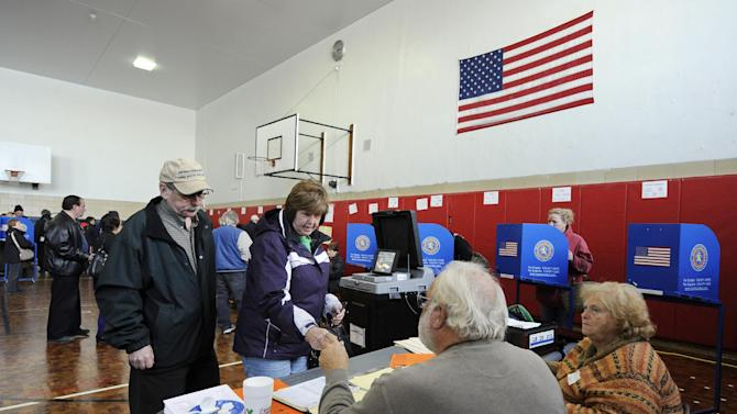 People line up to cast their votes in Lindell School, on Tuesday, Nov. 6, 2012, in Long Beach, N.Y., one of several voting locations that was created as a result of Superstorm Sandy.  Voting in the U.S. presidential election was the latest challenge for the hundreds of thousands of people in the New York-New Jersey area still affected by Superstorm Sandy, as they struggled to get to non-damaged polling places to cast their ballots in one of the tightest elections in recent history. (AP Photo/Kathy Kmonicek)