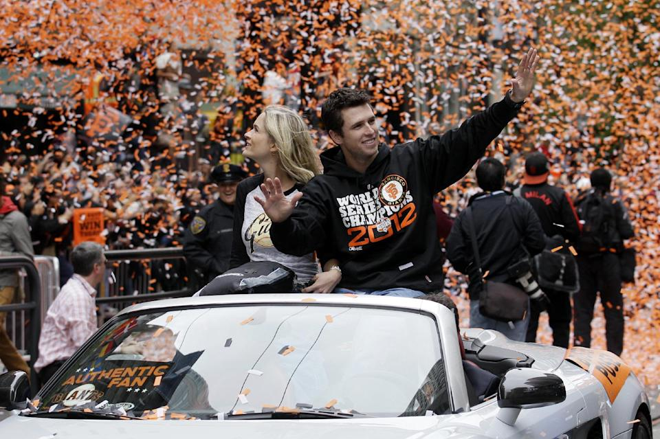 San Francisco Giants catcher Buster Posey and his wife Kristen ride in a car as confetti falls during the baseball team's World Series victory parade, Wednesday, Oct. 31, 2012, in San Francisco. (AP Photo/Jeff Chiu)