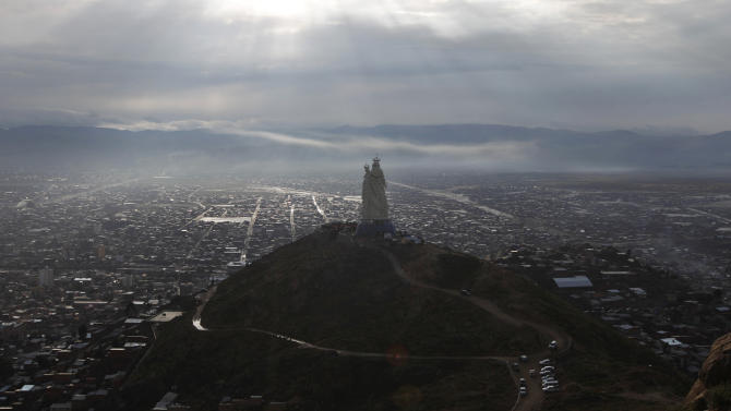 """A large statue of the Virgin Mary stands on Santa Barbara hill overlooking the mining city of Oruro, Bolivia, as it is unveiled on Friday, Feb. 1, 2013. The statue, known in Spanish as """"Virgen del Socavón,"""" or the Virgin of the Tunnel, is Oruro's patron, venerated in particular by miners and folkloric Carnival dancers. To withstand Bolivia's high plains' strong winds, the statue that stands at 45 meters (147 feet) was constructed with cement, metal and fiberglass. (AP Photo/Juan Karita)"""