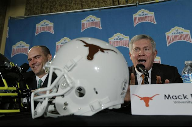 Oregon coach Mark Helfrich, left, and Texas coach Mack Brown, right, take part in a Valero Alamo Bowl news conference, Thursday,  Dec. 12, 2013, in San Antonio. Texas and Oregon will play in the NCAA