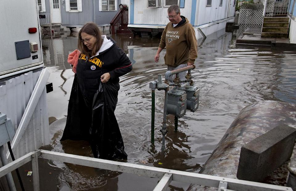 Using garbage bags to keep her waist dry, Mary Ann Tobias, and Walter Chaney of Moonachie, N.J. walk from their flooded home in the Metropolitan Trailer Park in Moonachie, N.J. Tuesday, Oct. 30, 2012 in the wake of superstorm Sandy. (AP Photo/Craig Ruttle)