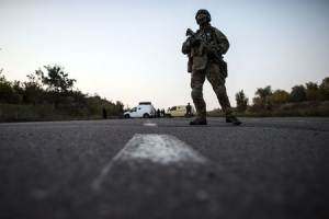A Ukrainian soldier stands guard on a road during a…