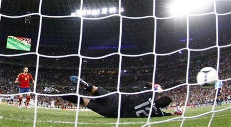 Spain's Cesc Fabregas (L) scores the winning penalty goal against Portugal's goalkeeper Rui Patricio during the penalty shoot-out in their Euro 2012 semi-final soccer match at the Donbass Arena in Donetsk, June 27, 2012. 