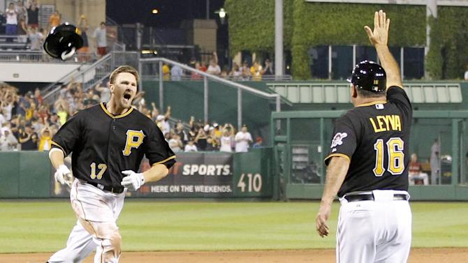 Pittsburgh Pirates' Drew Sutton (17) loses his helmet as he rounds third while third base coach Nick Leyva (16) greets him in the bottom of the ninth inning of the baseball game after hitting the game winning home run to lift the Pirates to an 8-7 win over the Houston Astros on Tuesday, July 3, 2012, in Pittsburgh. (AP Photo/Keith Srakocic)