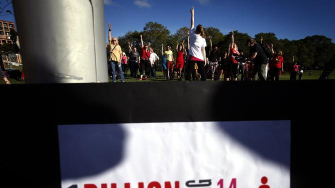 A group of women and men dance as they participate in an event labelled 'One Billion Rising' at a park in central Sydney