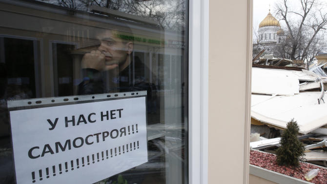 "A man looks out of the window decorated with a sign which reads ""Ours isn't a self-built building!"" during a demolition of illegal street kiosks and stalls near the Krapotkinskaya metro station"