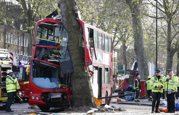 Members of the emergency services attend to a bus which crashed into a tree in Kennington, south London
