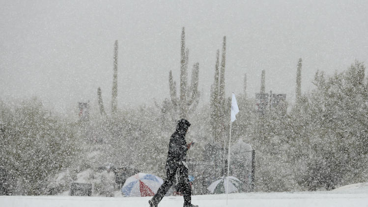 A volunteer walks along the practice green as snow falls during the Match Play Championship golf tournament, Tuesday, Feb. 19, 2013, in Marana, Ariz. Play was suspended. (AP Photo/Ross Franklin)