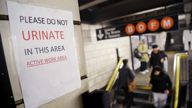 """A sign hangs in the West 4th Street subway station reads """"Please Do Not Urinate In This Area - Active Work Area,"""" Tuesday, March 3, 2015 in New York. The sign was posted by workers who are doing track work. """"That station is an area that is notorious for public urination,"""" said Kevin Ortiz, a spokesman for the agency that operates the system. Greenwich Village night-life patrons, homeless people and others all seem drawn to relieve themselves there, he added. (AP Photo/Mark Lennihan)"""