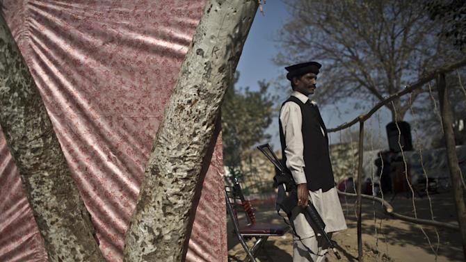 A Pakistani private security guard, stands guard by an outdoor Mass on Christmas Day, in a Christian neighborhood in Islamabad, Pakistan, Thursday, Dec. 25, 2014. (AP Photo/Muhammed Muheisen)
