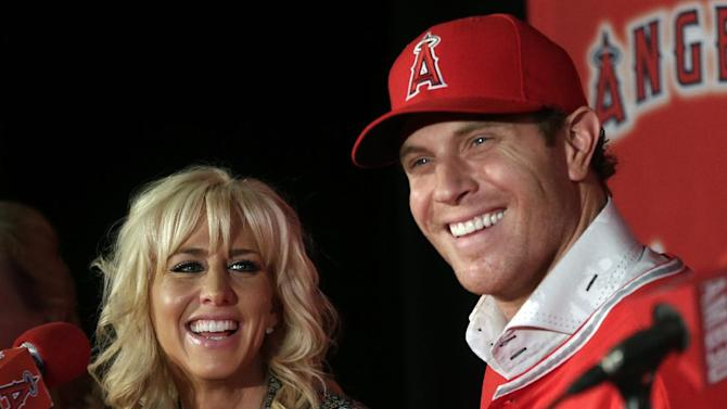 Free-agent outfielder Josh Hamilton, right, and his wife Katie, talk to the media during a news conference in Anaheim, Calif., Saturday, Dec. 15, 2012. Hamilton, formerly of the Texas Rangers, joins the Los Angeles Angels MLB baseball team after signing a $125 million, five-year contract. (AP Photo/Chris Carlson)