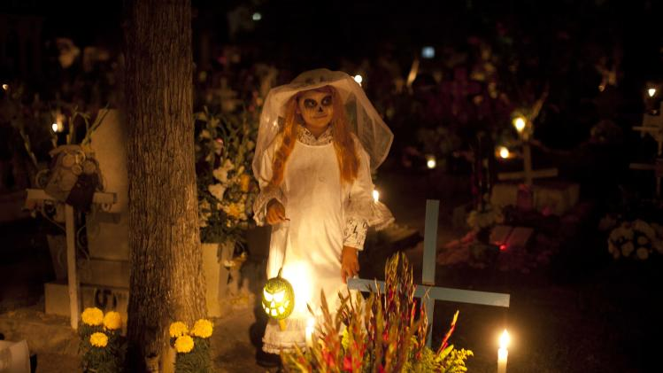 Frangerato Salvador, 8, dressed as a Katarina, stands beside her brother's grave, marking the Day of the Dead holiday at the cemetery in San Gregorio, Mexico, Thursday, Nov. 1, 2012. The holiday honors the dead on Nov. 1, coinciding with All Saints Day and All Souls' Day on Nov. 2. (AP Photo/Alexandre Meneghini)