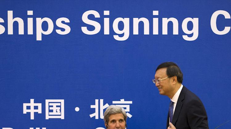 U.S. Secretary of State John Kerry, left, claps hand as Chinese State Councilor Yang Jiechi makes his way to deliver his speech during the China-U.S. EcoPartnerships signing ceremony at the Great Hall of the People in Beijing, China Thursday, July 10, 2014. (AP Photo/Andy Wong, Pool)