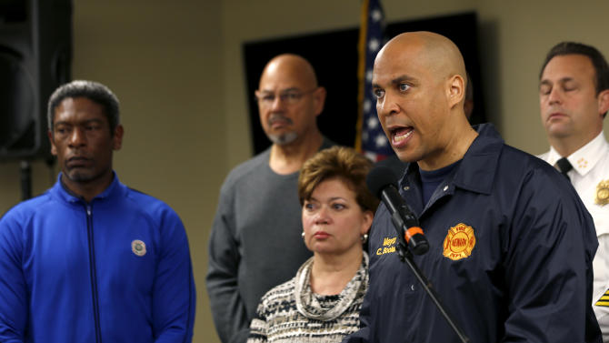 """FILE- In this Monday, Oct. 29, 2012, file photo, Newark Mayor Cory Booker, right, talks during a news conference at the Office of Emergency Management in preparation for the arrival of Hurricane Sandy, in Newark, N.J. Booker said Sunday, Dec. 9, 2012, that he'll decide within two weeks whether to challenge Republican Gov. Chris Christie next year. Booker, who leads the state's largest city, also told CBS' """"Face the Nation"""" that he's also thinking about running for the U.S. Senate. (AP Photo/Julio Cortez, File)"""