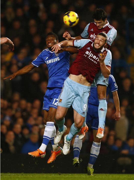 Chelsea's Mikel challenges West Ham United's Carroll and Tomkins during their English Premier League soccer match at Stamford Bridge in London