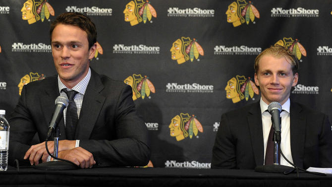 Chicago Blackhawks players Jonathan Toews, left,  and Patrick Kane listen during a news conference at the United Center in Chicago, Wednesday, July 16, 2014. The Blackhawks recently agreed to eight-year contract extensions with for their star players