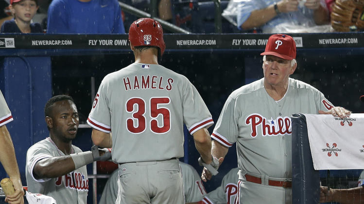 Philadelphia Phillies starting pitcher Cole Hamels (35) is greeted by manager Charlie Manuel, right, at the dugout afer scoring on a Jimmy Rollins base hit in the third inning of a baseball game in Atlanta, Monday, Aug. 12, 2013. (AP Photo/John Bazemore)