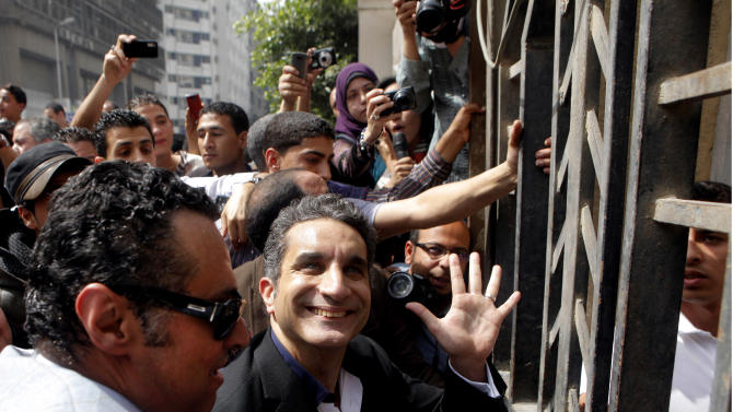 Egyptian popular television satirist Bassem Youssef, who has come to be known as Egypt's Jon Stewart, waves to is supporters as he enters Egypt's state prosecutors office to face accusations of insulting Islam and the country's Islamist leader in Cairo, Egypt, Sunday, March 31, 2013. Government opponents said the warrant against such a high profile figure, known for lampooning President Mohammed Morsi and the new Islamist political class, was an escalation in a campaign to intimidate critics. (AP Photo/Amr Nabil)
