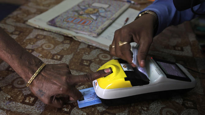 FILE-  In this March 20, 2012 file photo, an impoverished woman places her finger on a biometric card reader before buying her quota of subsidized rice from a fair price shop under the Public Distribution System in Rayagada, in Indian eastern state of Orissa. India will send billions of dollars in social welfare money directly to its poor under a new program inaugurated Tuesday, Jan. 1, 2013, aiming to cut out the middlemen blamed for the massive fraud that plagues the system. The new program would see welfare money directly deposited into recipients' bank accounts and require them to prove their identity with biometric data, such as fingerprints or retina scans.  (AP Photo/Manish Swarup, File)