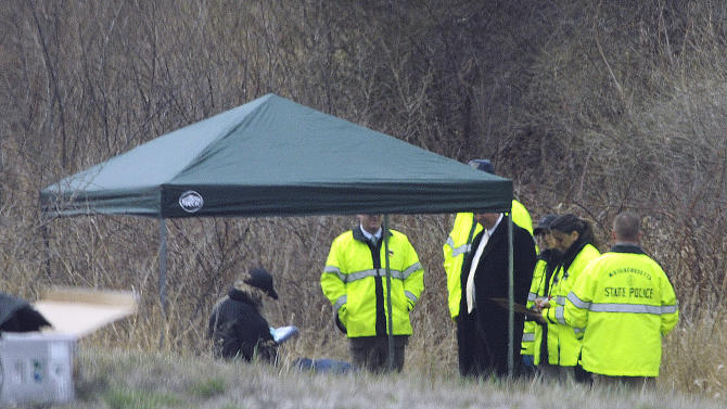 Massachusetts State Police stand along Interstate 190 where police said a child's body was found