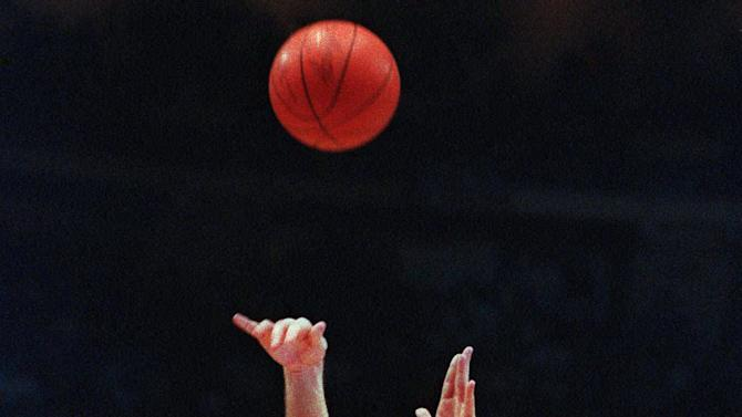 """FILE - In this March 28, 1992, file photo, Duke's Christian Laettner takes the winning shot in overtime over Kentucky's Deron Feldhaus for a 104-103 victory in the East Regional Final NCAA college basketball game in Philadelphia. For the first time since Laettner's improbable buzzer-beater, head coaches Mike Krzyzewski and Rick Pitino are meeting in the regional finals of the NCAA tournament. Pitino is across the state in Louisville these days, but that doesn't lessen the drama of their long-awaited """"rematch."""" (AP Photo/Charles Arbogast, File)"""