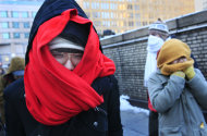 **CORRECTS CELSIUS TEMPERATURE TO -15 C, NOT -40C** Quynh-Mi Le, left, waits for a bus on a New York street corner, Monday, Jan. 24, 2011. New York City area residents woke up to bone-chilling temperatures of 5-degrees Fahrenheit (-15 C).