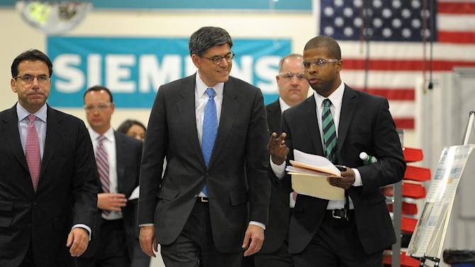 Treasury Secretary Jacob Lew, center, tours the Siemens Industry manufacturing plant with company CEO Helmuth Ludwig, left, where electrical drive components for heavy machinery are assembled in Alpharetta, Ga., Thursday, March 14, 2013. The facility produces large traction drive trains for customers including AMTRAK, Caterpillar and the new Atlanta Streetcar initiative. (AP Photo/David Tulis)