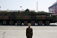 A North Korean soldier stands guard in front of a military vehicle carrying what is believed to be a Taepodong-class missile during a military parade in Pyongyang in April 2012. North Korea plans to launch a long-range rocket between December 10 and 22, the North&#39;s official news agency said Saturday