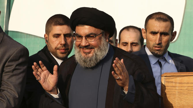 In this Monday, Sept. 17, 2012 photo, Hezbollah leader Sheik Hassan Nasrallah, center, waves to his supporters, in the southern suburb of Beirut, Lebanon. The leader of the Lebanese militant Hezbollah group has claimed responsibility for launching the drone aircraft that entered Israeli airspace earlier this week. The rare admission Thursday by Hassan Nasrallah raises regional tensions at a sensitive time when the group's backers, Syria and Iran, are under pressure. (AP Photo/Hussein Malla)