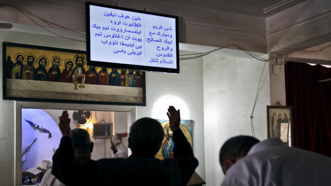 In this Wednesday, March 27, 2013 photo, Egyptians celebrate mass, reading the Arabic service on a computer screen, in the Coptic Orthodox Church in Samalout, in the province of Minya, Egypt. In Minya where Christians make up about 35 percent of the population,  kidnapping wealthy Christians for ransom is not unheard of, but  30 cases in the last two months alone, has given to soul searching about being a Christian in a country where Muslims are an overwhelming majority and Islamists, including many hardliners, have risen to power.(AP Photo/Thomas Hartwell)