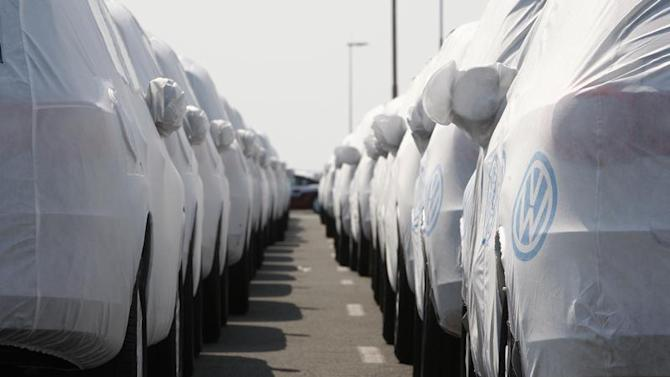 New VW cars are covered with protective covers before loaded for export on a transport ship at the harbour in Emden