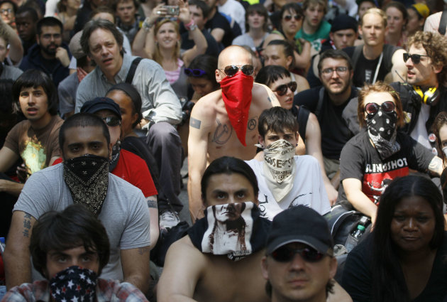 Occupy Chicago protesters, some wearing masks, sit in the street outside Mayor Rahm Emaunel's house during a march and demonstration in Chicago Saturday, May 19, 2012. Security has been high throughou