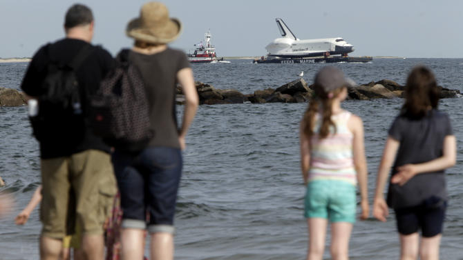 Spectators watch the space shuttle Enterprise as it is towed past a beach at Coney Island in New York, Sunday, June 3, 2012.  The prototype space shuttle that arrived in New York City by air earlier this spring is on the move again, this time by sea, to it's final resting place at the Intrepid Sea, Air and Space Museum on the west side of Manhattan. (AP Photo/Seth Wenig)