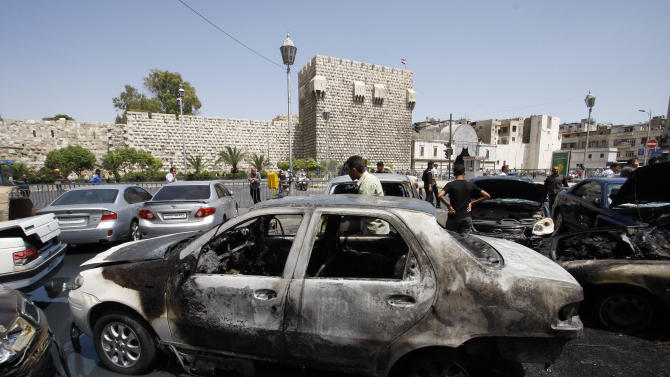 Syrians inspect burned cars at the site of a blast in the Syrian capital Damascus Thursday June 28, 2012. A strong explosion rocked the Syrian capital Thursday near a busy market and the Palace of Justice, sending black smoke billowing into the sky. State TV reported at least three people were wounded and around 20 cars were damaged. (AP Photo/Muzaffar Salman)