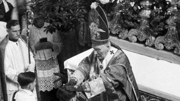 FILE -  In this June 29, 1951 file photo, Cardinal Michael von Faulhaber, top, blesses Joseph Ratzinger during his ordination to the priesthood in the Freising, southern Germany, cathedral. Ratzinger, who later became Pope Benedict XVI, announced Monday, Feb. 11, 2013 that he will resign on Feb. 28. The 85-year-old pope announced his decision in Latin during a meeting of Vatican cardinals. (AP Photo/dpa, Archdiocese Munich)