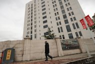 "A man walks past a 12-storey building alleged in a report on February 19, 2013 by the Internet security firm Mandiant as the home of a Chinese military-led hacking group. Chinese state media stepped up the war of words Thursday over allegations of sophisticated cyberattacks on US firms, branding the accusations a ""commercial stunt"" and accusing Washington of ulterior motives"