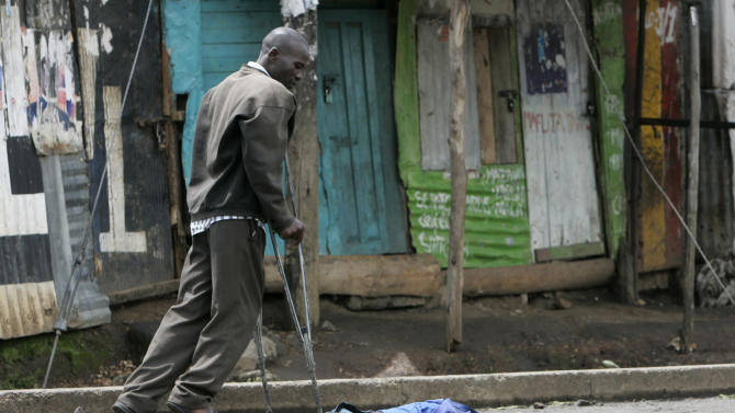 FILE - In this Sunday, Jan. 20, 2008 file photo, a man on crutches walks past the body of a man killed during ethnic fighting and post-election violence in the Mathare slum of Nairobi, Kenya. Kenya's first nation-wide vote since devastating violence broke out after the nation's 2007 presidential election will be closely monitored by the international community and local observers to help ward off potential problems, officials said Monday, Jan. 28th, 2013. (AP Photo/Karel Prinsloo, File)