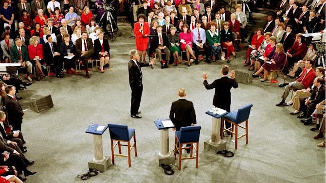 "FILE - In this Oct. 15, 1992 file photo,  Moderator Carole Simpson, background center, presides over the Presidential debate between, from left, Democratic presidential candidate Bill Clinton, Independent candidate Ross Perot, center, and Republican candidate, President George H.W. Bush, at the University of Richmond, Va. The every-four-years ritual of a national ""town hall"" style debate began as a nerve-racking experiment in live television. Simpson was so nervous about turning over the microphone to regular folks and their questions that she spent days mapping out the presidential candidates and their issues on ""a zillion 3-by-5 cards,"" in case she had to take over the questioning herself. (AP Photo/Joe Marquette, File)"