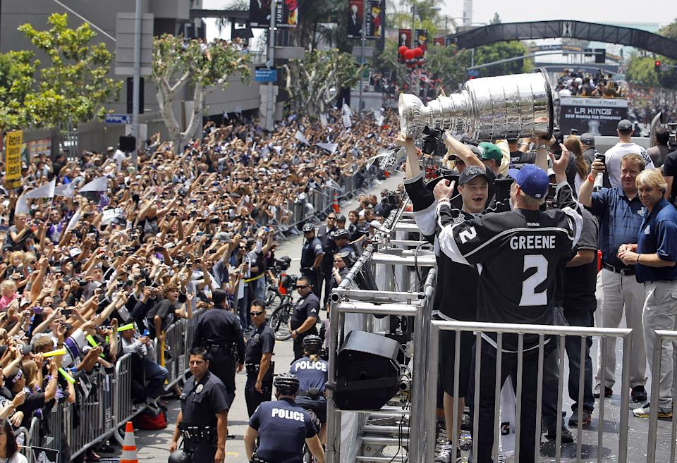 Los Angeles Kings' Matt Greene (2) and teammate Dustin Brown hoist the Stanley Cup during a parade celebrating the team's NHL hockey Stanley Cup championship during a parade in Los Angeles, Thursday, June 14, 2012. (AP Photo/Jae C. Hong)