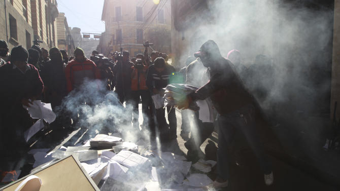 Police demanding higher wages burn documents outside a police internal affairs building, in La Paz, Bolivia, Friday, June 22, 2012. Protesters were demanding salaries on par with soldiers and a pension equal to 100 percent of their salaries. Bolivian police earn about $144 a month and were not appeased by a 7 percent government-decreed wage increase this year. (AP Photo/Juan Karita)