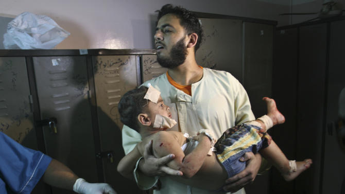"A Palestinian man carries a wounded boy in Al Najar Hospital following an Israeli air strike in Rafah, southern Gaza Strip, Sunday, Oct. 7, 2012. Israel's military says it has fired on two Gaza members of an al-Qaida-inspired group identified as having been involved in rocket attacks and an infiltration from Egypt. Palestinians say one man was killed. The military said they were involved in ""extensive terrorist activity,"" including an attack in June where two gunmen crossed into Israel from the Sinai desert and killed a civilian.Israel did not say whether it hit the two. Ashraf al-Kidra, a Palestinian health official in Gaza said one man was killed and another injured Sunday when their motorcycle was hit by aircraft in the south of the Hamas-controlled territory. Israel and Hamas have mostly kept an unwritten truce since a short war over three years ago. Attacks have persisted but at a much lower rate. (AP Photo/Eyad Baba)"
