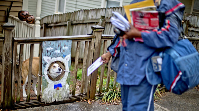 U.S. Postal Service letter carrier of 12 years, Jamesa Euler, encounters a barking a dog while delivering mail in the Cabbagetown neighborhood, Thursday, Feb. 7, 2013, in Atlanta. The financially struggling U.S. Postal Service wants to stop delivering mail on Saturdays but continue to deliver packages six days a week under a plan aimed at saving about $2 billion a year. (AP Photo/David Goldman)