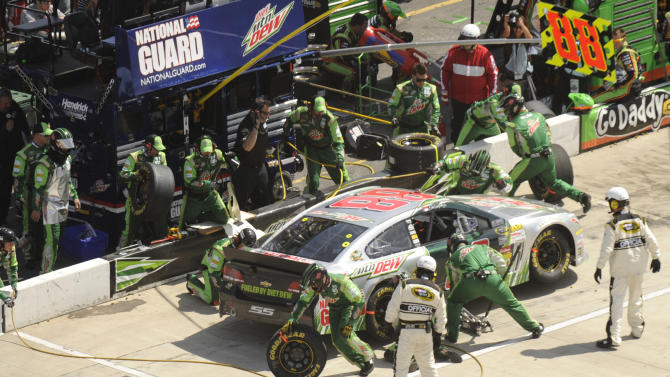 The pit crew for Dale Earnhardt Jr. (88) works on the car in the pits during the STP 500 NASCAR Sprint Cup series auto race at Martinsville Speedway in Martinsville, Va., Sunday, April 7, 2013. (AP Photo/Don Petersen)