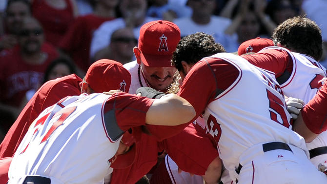 FILE - In this May 29, 2010, file photo, Los Angeles Angels Kendrys Morales (8) reacts after breaking his left ankle while jumping onto home plate after hitting a grand slam to win their baseball game against the Seattle Mariners, in Anaheim, Calif. The Angels have traded power hitter Morales to the Mariners for left-hander Jason Vargas. (AP Photo/Mark J. Terrill, File)