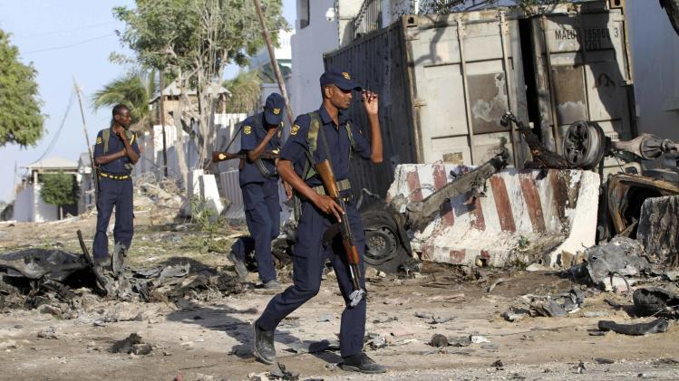 Security guards assess the aftermath at the scene of an explosion outside Jazira hotel in Mogadishu