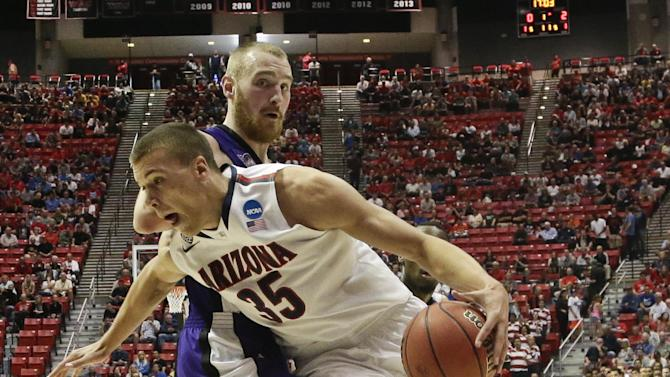 Arizona center Kaleb Tarczewski spins around Weber State center Kyle Tresnak while going to the basket during the first half in a second-round game in the NCAA college basketball tournament Friday, March 21, 2014, in San Diego. (AP Photo/Gregory Bull)