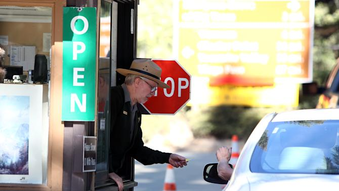 Yosemite Park Ranger Ron Morton takes a payment from a visitor at the front gate after the reopening of Yosemite National Park, Calif., Thursday, Oct. 17, 2013. The park reopened Wednesday night with the end of the 16-day partial government shutdown. (AP Photo/Gary Kazanjian)