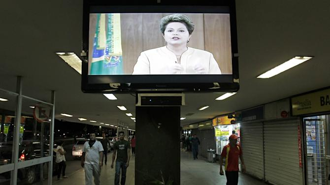A message by Brazil's President Dilma Rousseff is broadcast live at the bus station in Brasilia, Brazil, Friday, June 21, 2013. The Brazilian ended her near-silence about more than a week of massive, violent protests, saying in a prime time TV broadcast Friday that peaceful demonstrations were part of a strong democracy but that violence could not be tolerated. She promised to make improvements to public services, but said it couldn't be done overnight. (AP Photo/Eraldo Peres)