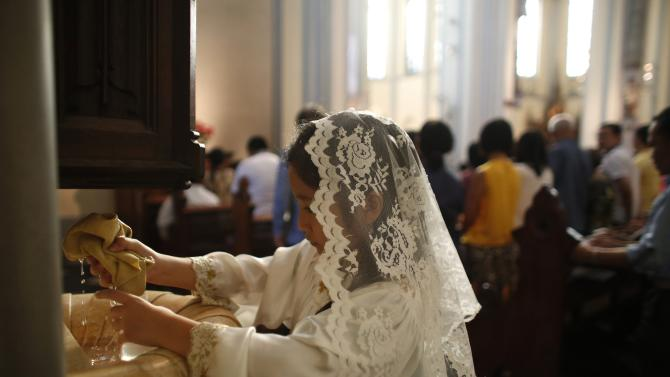 A Catholic altar girl changes the Holy Water at the start of a mass on Christmas day at Jakarta Cathedral in Jakarta